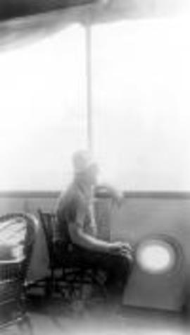 An old photo of President Franklin D Roosevelt,sitting on a boat in a wheelchair, looking out over the side toward the sea.