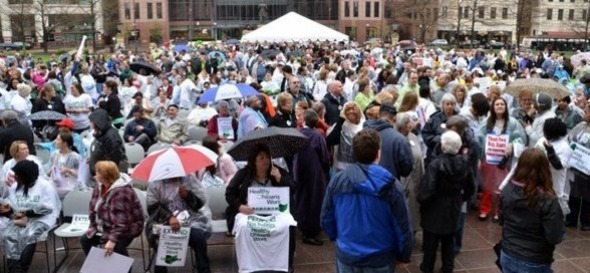 Photo of demonstrators, standing or sitting in the rain, advocating for health care.