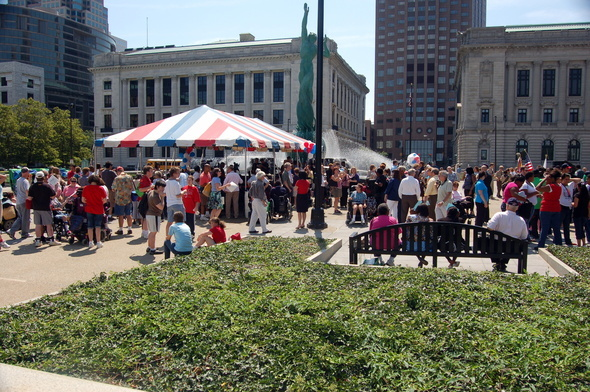 Photo of downtown park with a red, white and blue tent and large groups of individuals under and outside of the tent during an advocacy event.