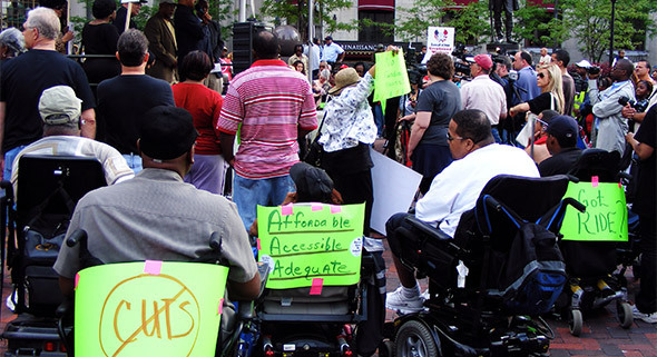 Photo of activists facing a stage.  Some of the activists are holding lime green signs advocating for disability rights.
