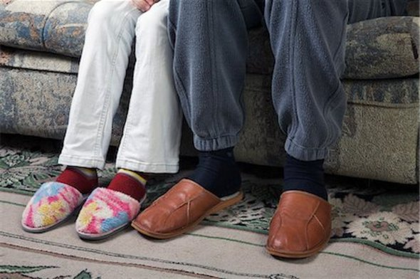 Close-up of a couple sitting on a couch with their leg/foot touching from the knees down.